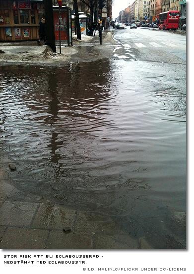 ett gathörn översvämmat av smutsigt smältvatten