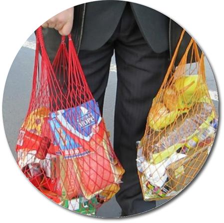 man bär ryska matvaror i två nätkassar