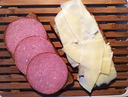 en limpsmörgås med ost och en med priclig korv